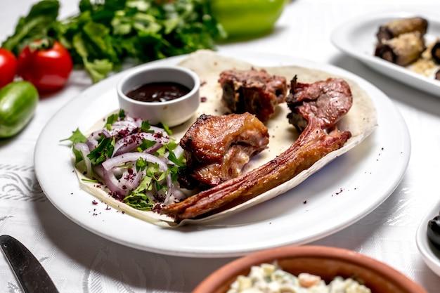 Vista lateral tike kebab en pan de pita con hierbas y cebollas con salsa y verduras