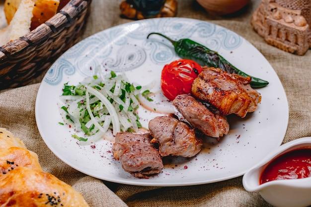 Vista lateral tikya kebab con cebolla verde salsa de tomate picante picante y pan sobre la mesa