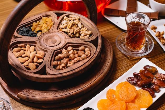 Vista lateral de un tipo de nueces en una bandeja con un vaso de té y frutas secas