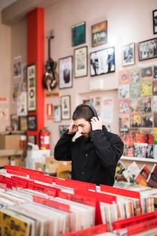 Vista lateral de tiro medio de un hombre joven escuchando música en una tienda de vinilo