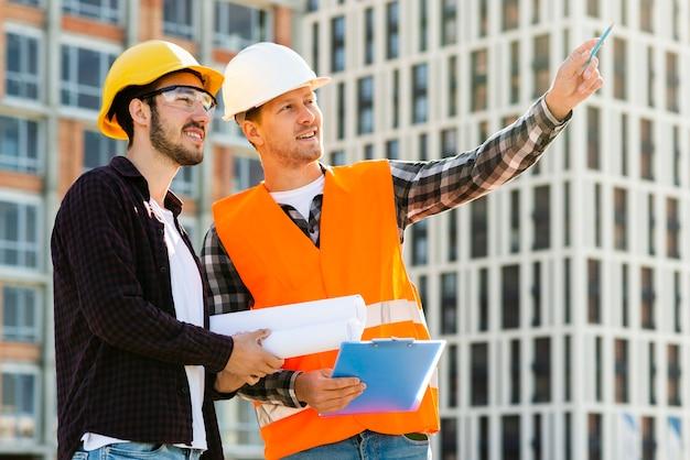 Vista lateral de tiro medio de ingeniero y arquitecto mirando edificio