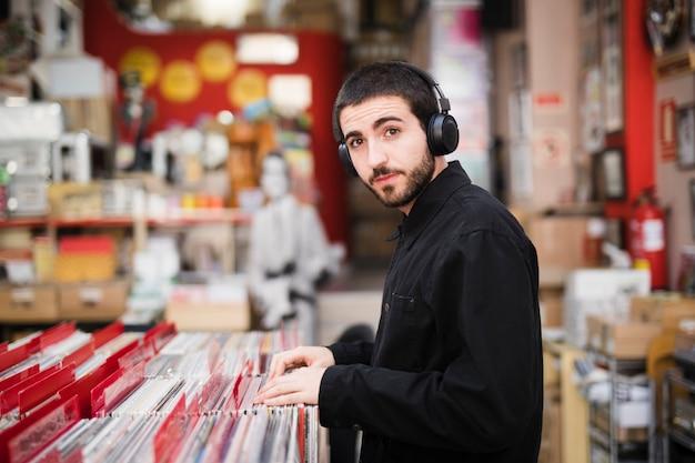 Vista lateral de tiro medio de un joven mirando a la cámara en una tienda de vinilo