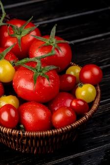 Vista lateral de tomates amarillos y rojos en canasta sobre superficie de madera