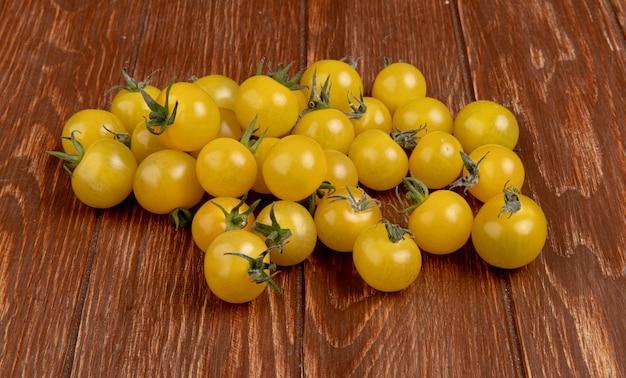 Vista lateral de tomates amarillos sobre superficie de madera