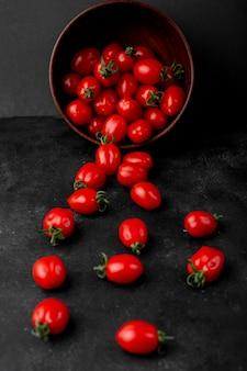 Vista lateral de tomates cherry maduros frescos esparcidos del tazón de madera sobre fondo negro