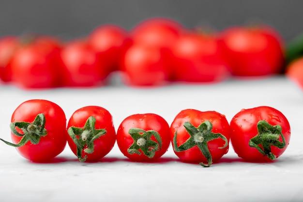 Vista lateral de tomates cherry maduros sobre fondo blanco.