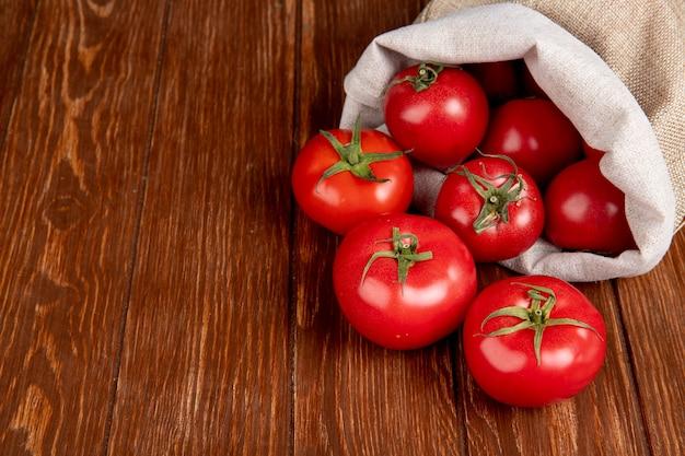 Vista lateral de tomates derramando saco en el lado derecho y mesa de madera con espacio de copia