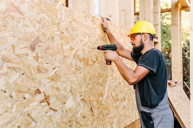 Vista lateral del trabajador de la construcción de perforación en madera contrachapada con espacio de copia