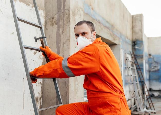 Vista lateral del trabajador con máscara protectora subiendo una escalera