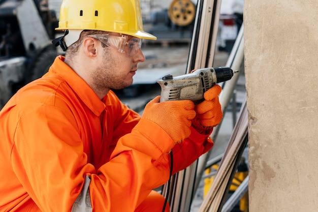Vista lateral del trabajador masculino con casco y gafas protectoras