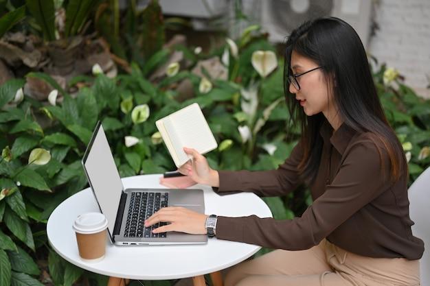 Vista lateral de la trabajadora de oficina sosteniendo el libro de horarios y trabajando con la computadora portátil en la mesa redonda en el jardín en casa
