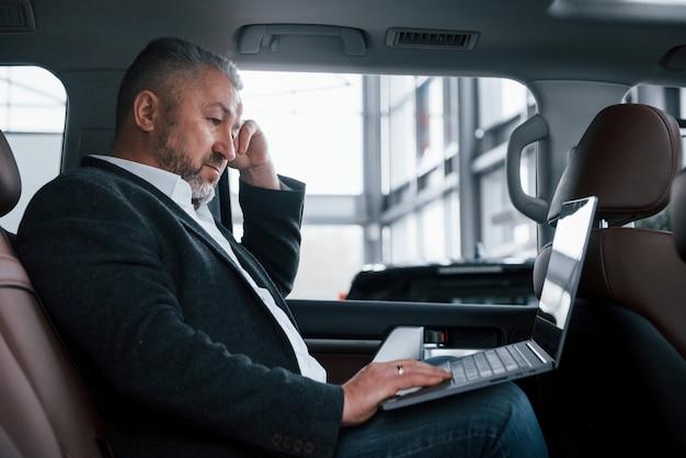 Vista lateral. trabajando en la parte trasera del coche usando una computadora portátil de color plateado. hombre de negocios mayor