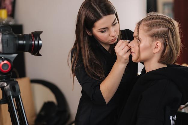 Vista lateral del trabajo del artista de maquillaje con hermosa modelo de cabello rubio en estudio hasta que filma la cámara