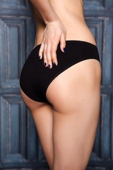 Vista lateral del trasero y la mano de la mujer apoyada en su trasero