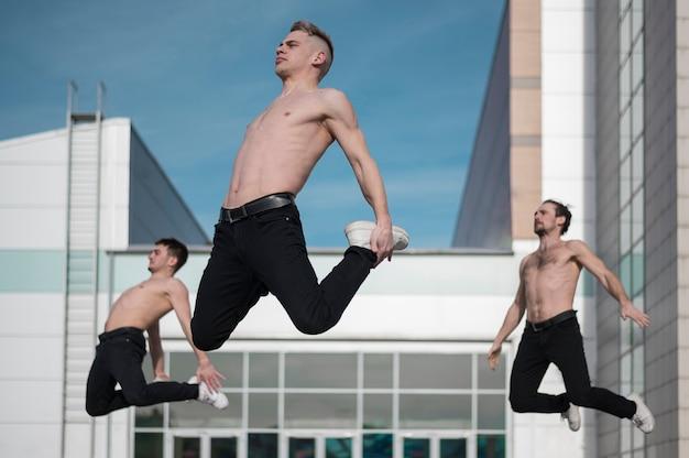 Vista lateral de tres bailarines de hip hop sin camisa posando en el aire