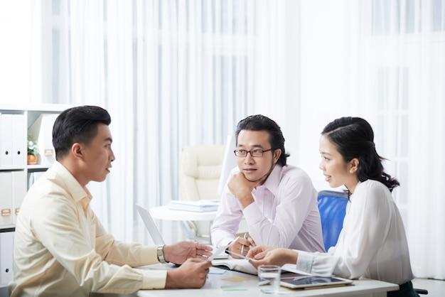 Vista lateral de tres colegas discutiendo el proyecto sentados en el escritorio de la oficina