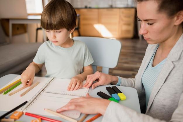 Vista lateral del tutor femenino enseñando a un niño en casa