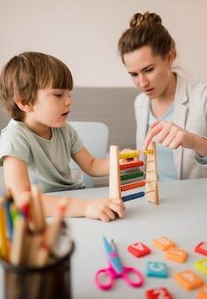 Vista lateral del tutor que le enseña al niño cómo usar un ábaco