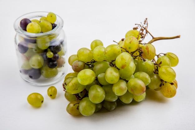 Vista lateral de uva blanca y bayas de uva en tarro sobre fondo blanco.