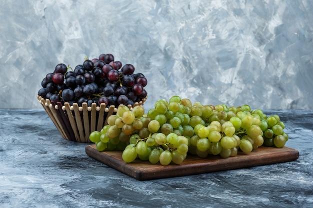 Vista lateral de uvas en canasta sobre yeso sucio y fondo de tabla de cortar. horizontal