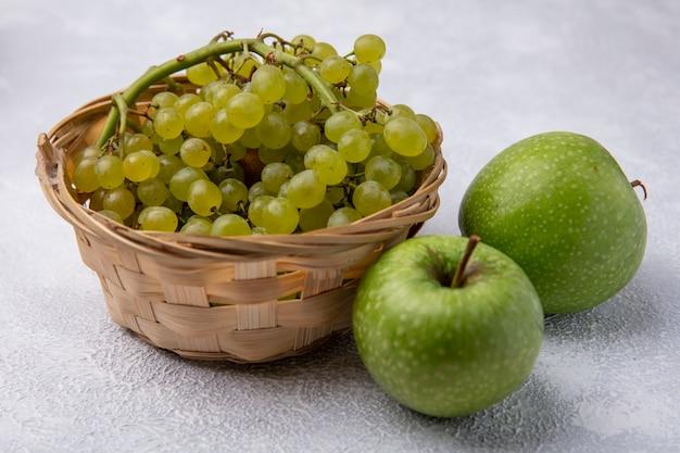 Vista lateral de uvas verdes en una canasta con manzanas verdes sobre un fondo blanco.