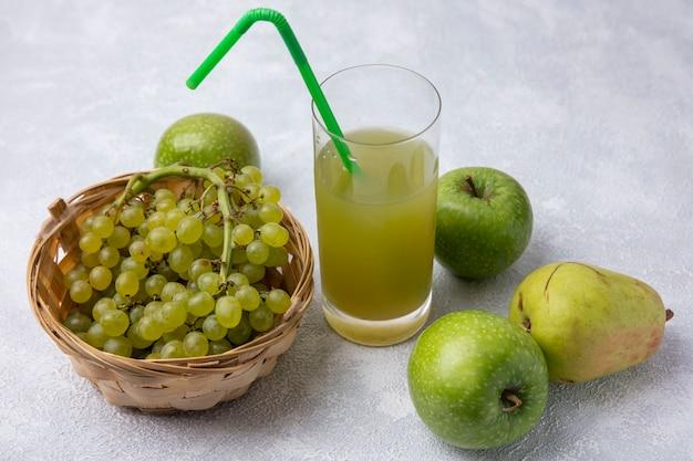 Vista lateral de uvas verdes en una canasta con pera manzanas verdes y jugo de manzana con una pajita verde en un vaso sobre un fondo blanco.