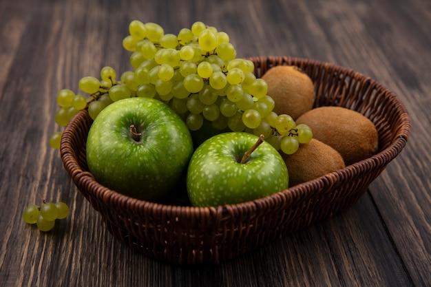 Vista lateral de uvas verdes con manzanas y kiwi en una canasta sobre un fondo de madera