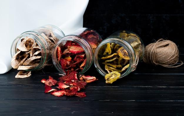 Vista lateral de varias rodajas de frutas secas dispersadas de frascos de vidrio sobre fondo negro