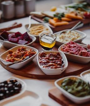 Vista lateral de varias salsas y ensaladas con verduras en una tabla de madera y aceite de oliva en el medio