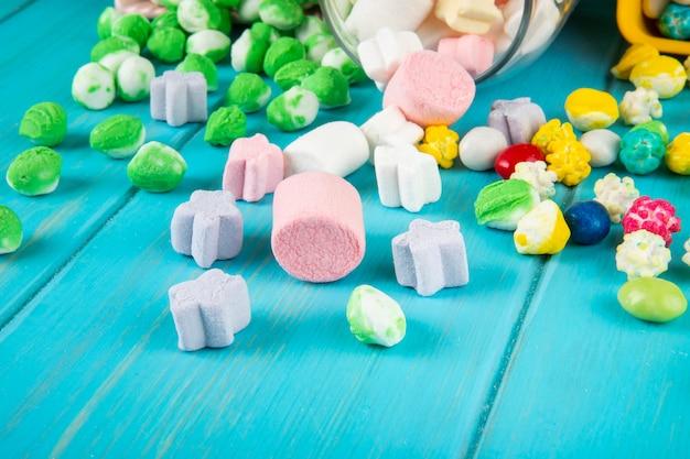 Vista lateral de varios caramelos de colores y malvaviscos esparcidos desde un frasco de vidrio sobre fondo azul.