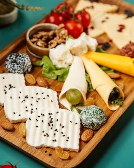 Vista lateral de varios tipos de queso con nueces uvas y tomates cherry en bandeja de madera