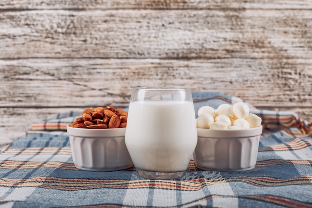Vista lateral vaso de leche con almendras, avellanas en un tazón en madera gris y fondo de tela de picnic azul. horizontal