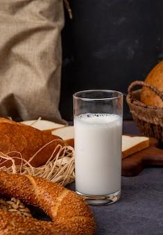 Vista lateral del vaso de leche con bagel sobre superficie marrón y fondo negro con espacio de copia