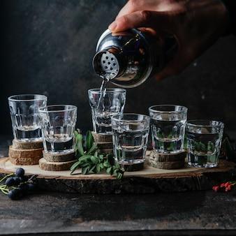 Vista lateral vasos de chupito con bebidas, barman vierte alcohol