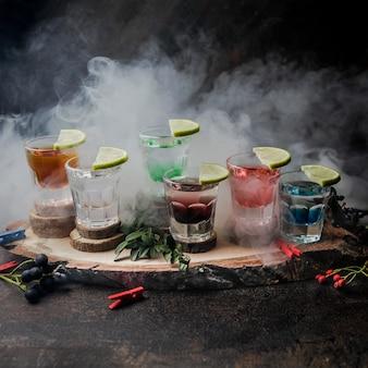 Vista lateral vasos de chupito con bebidas de color y lima