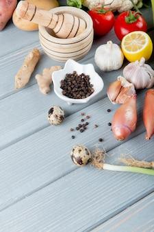 Vista lateral de verduras como cebolla ajo jengibre huevo tomate con pimienta negra sobre fondo de madera con espacio de copia