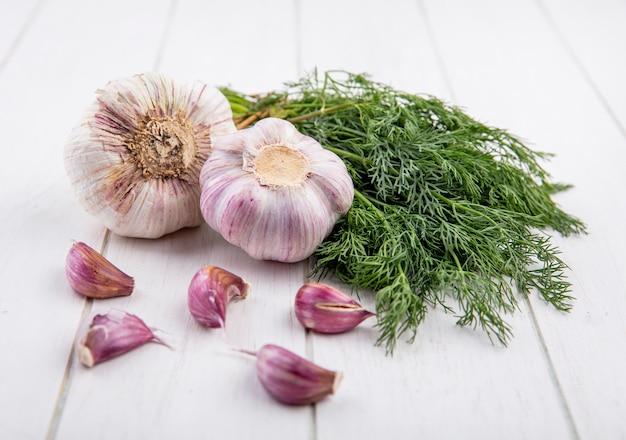 Vista lateral de verduras como manojo de eneldo y bulbo de ajo con dientes de ajo sobre madera