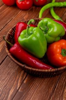 Vista lateral de verduras frescas coloridos pimientos chiles rojos en una cesta de mimbre en la mesa rústica de madera