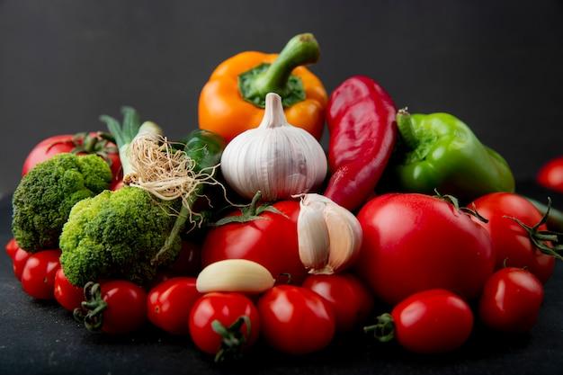 Vista lateral de verduras frescas maduras coloridos pimientos tomates ajo brócoli y cebolla verde sobre fondo negro