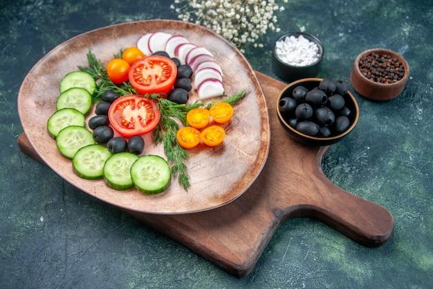 Vista lateral de verduras frescas picadas en una placa marrón sobre tabla de cortar de madera aceitunas en un tazón flor de ajos de sal sobre fondo de colores mezclados