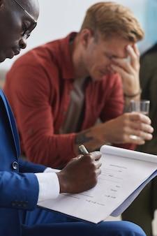 Vista lateral vertical en el psicólogo afroamericano masculino escribiendo en el portapapeles mientras dirige la sesión del grupo de apoyo, espacio de copia