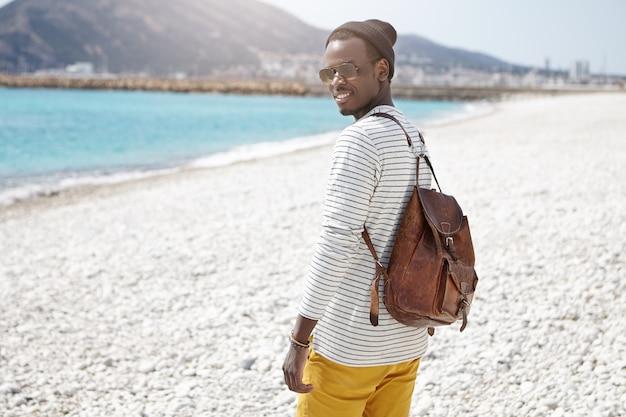 Vista lateral del viajero afroamericano con sombrero y gafas de sol de moda, con mochila al hombro