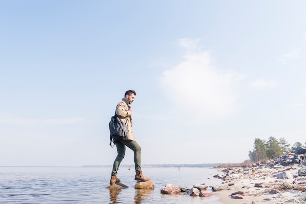 Vista lateral de un viajero masculino con su mochila de pie sobre las piedras en el lago