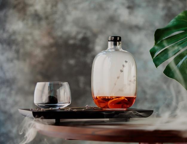 Vista lateral de vino caliente en una botella decorativa de vidrio sobre una tabla de madera