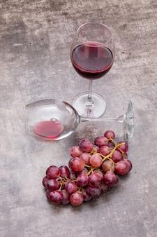 Vista lateral vino tinto en copas y uva en piedra oscura vertical