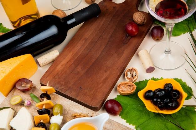 Vista lateral de vino tinto con diferentes tipos de queso mantequilla de oliva en tabla de cortar y corchos de nuez vino blanco sobre fondo blanco.