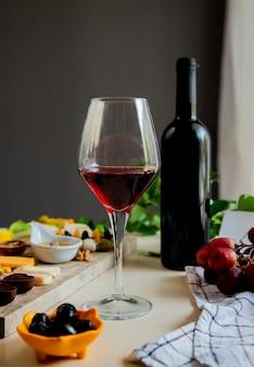 Vista lateral de vino tinto con diferentes tipos de queso uva nogal oliva sobre fondo blanco.