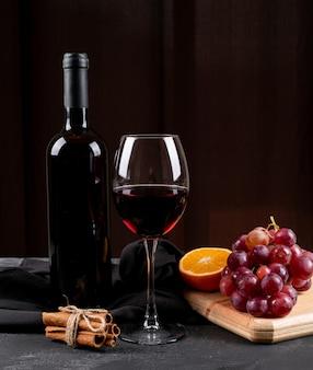 Vista lateral vino tinto con uva, naranja en tabla de cortar de madera en vertical oscuro