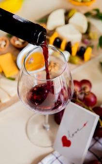 Vista lateral de vino tinto vertiendo en vidrio y diferentes tipos de queso de oliva, nuez, uva y tarjeta de amor sobre fondo blanco.