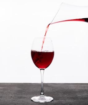 Vista lateral vino tinto en vidrio en blanco vertical